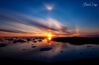 Sunset over Disko Bay with circular halo effect Greenland landscape