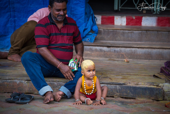 Baby with head covered with sandalwood paste outside Meenakshi Temple madurai India