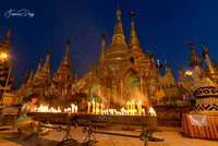 Woman light candle in front of Shwedagon Pagoda in Yangon Myanmar Buddha stupa