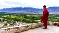 Young monk on Thiksey gompa roof watching Indus valley landscape Ladakh
